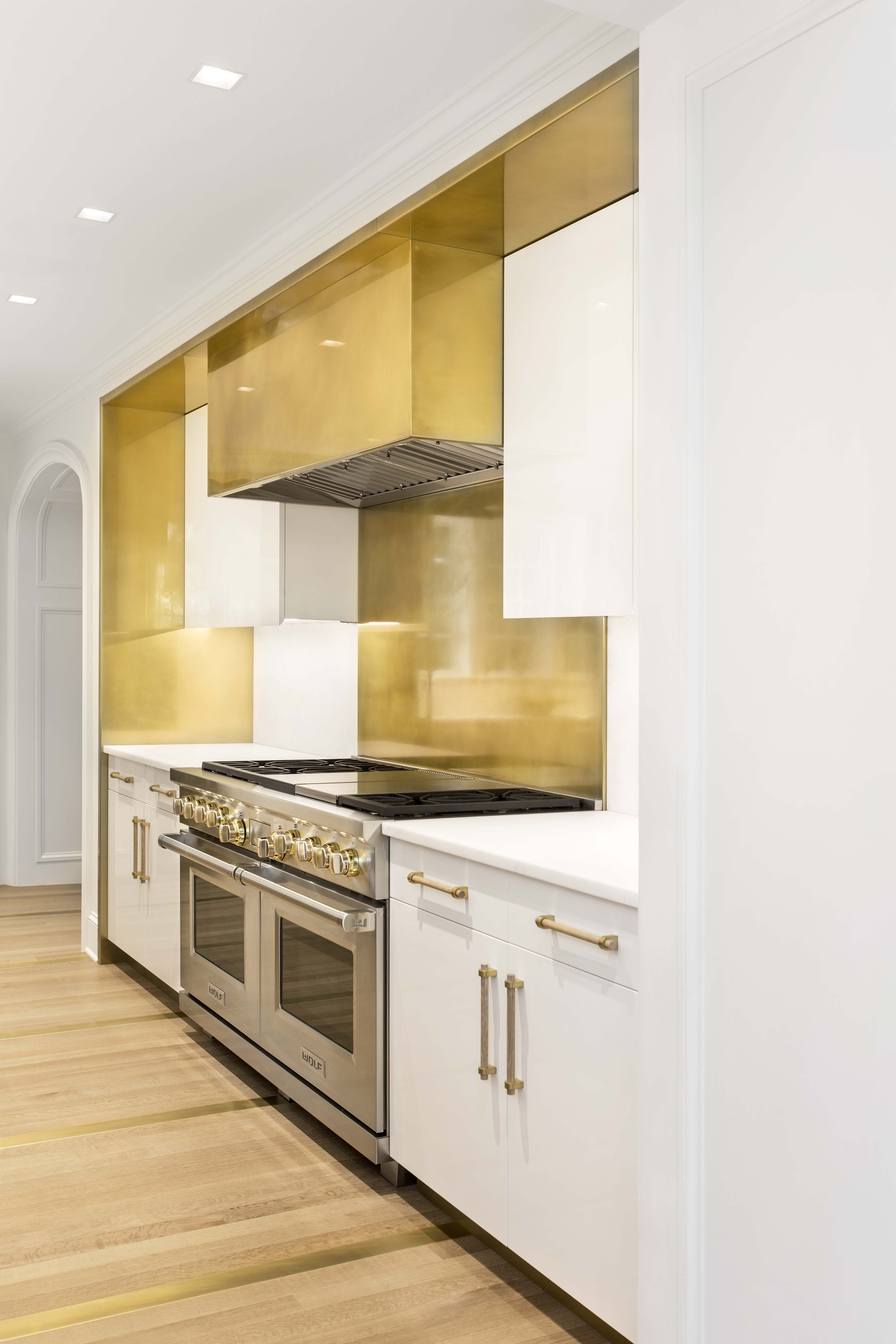 A Brass Kitchen Back Splash Allows For A Clean Contrast With The Polished Lacquer White Oa Kitchen Cabinets And Backsplash Brass Kitchen Kitchen Remodel Layout
