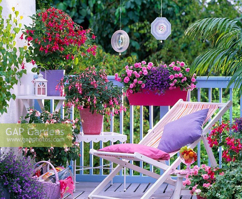 Photo of Balcony garden with reclining chair and mixed container plantings of Fuchsia, Im…
