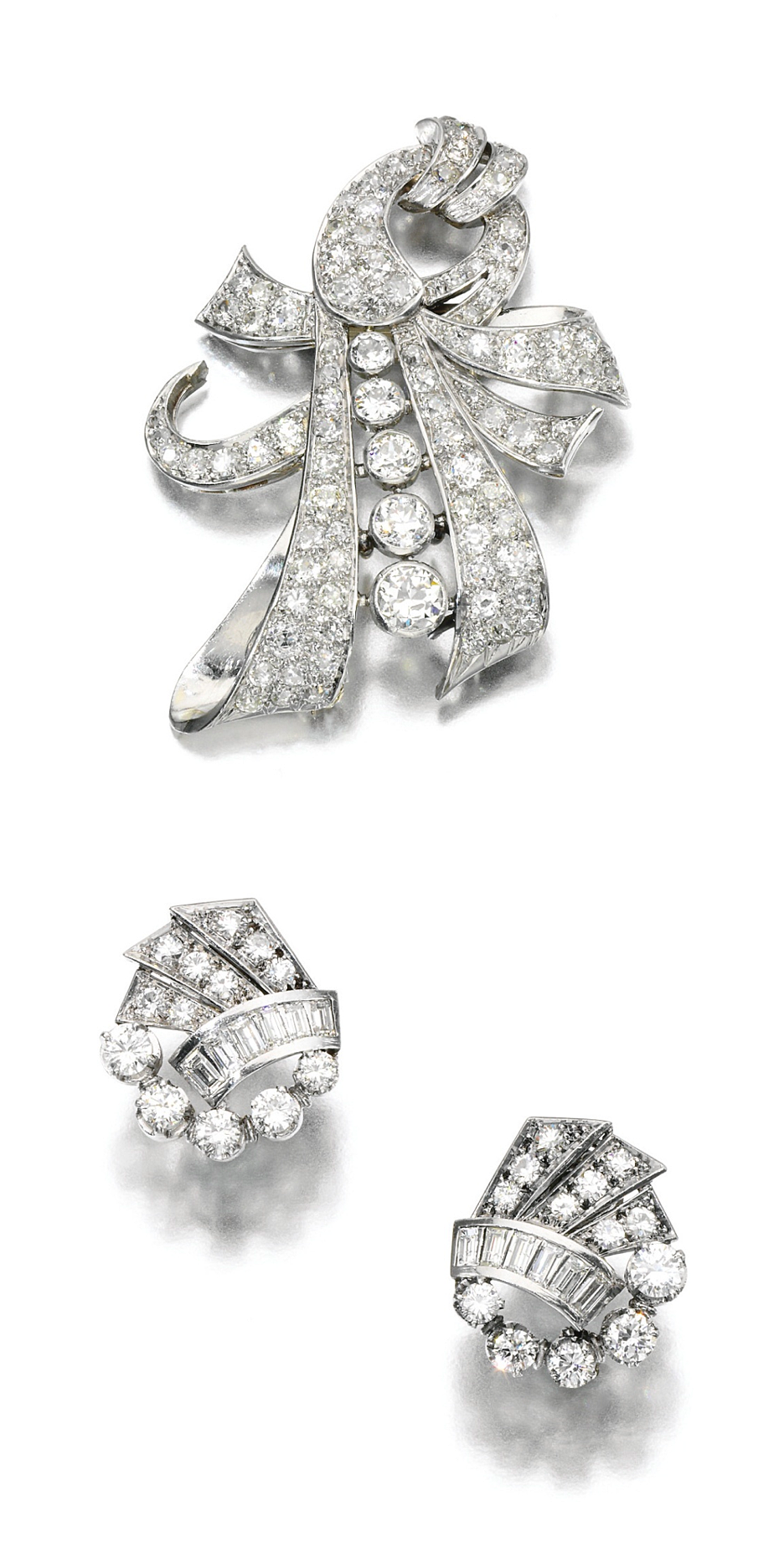 DIAMOND BROOCH AND PAIR OF EAR CLIPS, 1930S.  The brooch of open work ribbon scroll design set with circular- and single-cut diamonds and a pair of diamond ear clips of similar design set with circular-cut and baguette diamonds, French assay marks.