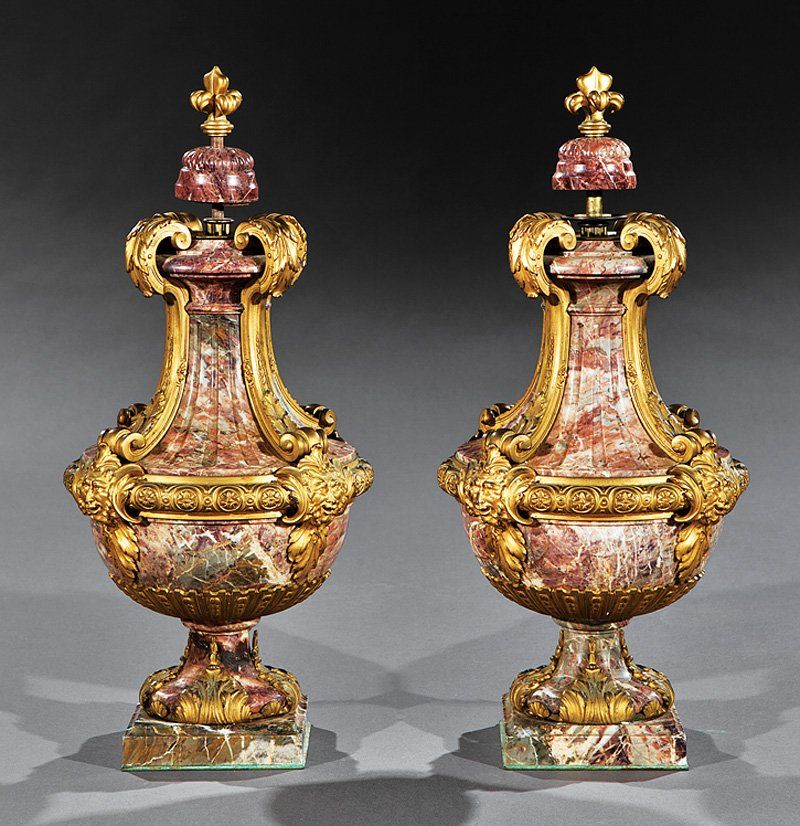 A Very Fine Pair of French 19th Century Louis XV Style Rouge Vriegated Marble and Figural Ormolu Mounted Urns by Ferdinand Barbedienne (French, d. 1892), the fluted body surmounted with gilt-bronze floral scrolls, acanthus and masks, now fitted with plate glass tops (later) for use as cocktail tables (removable). Both urns signed F. Barbedienne, Fondeur. Circa: Paris, 1880. Ferdinand Barbedienne (d. 1892) began his Parisian foundry in 1839, eventually becoming one of the most active and ...