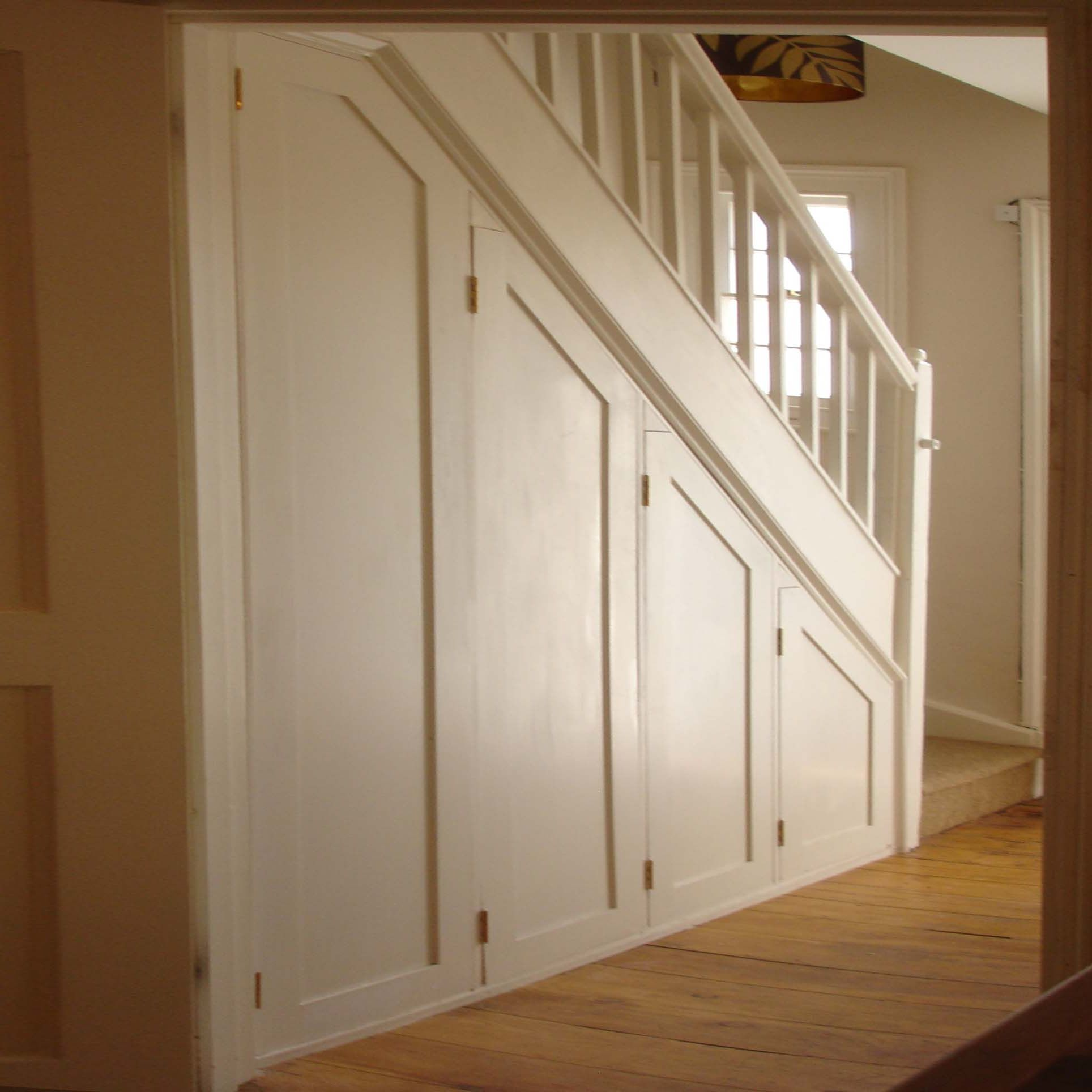 cupboard under the stairs with concertina doors that open