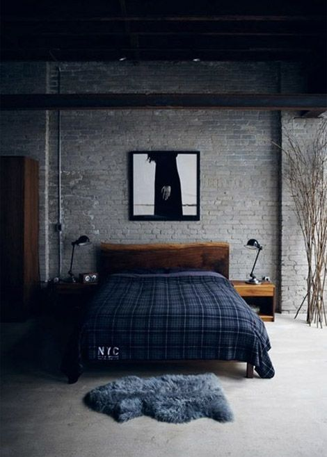 A harmonious blend of dark blues, pewter grey brick walls, and dark wood furniture create a cozy, cave-feel and give the room a masculine ambiance.