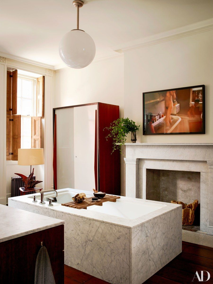 A Nan Goldin photograph hangs in the master bath. Kohler tub with ...