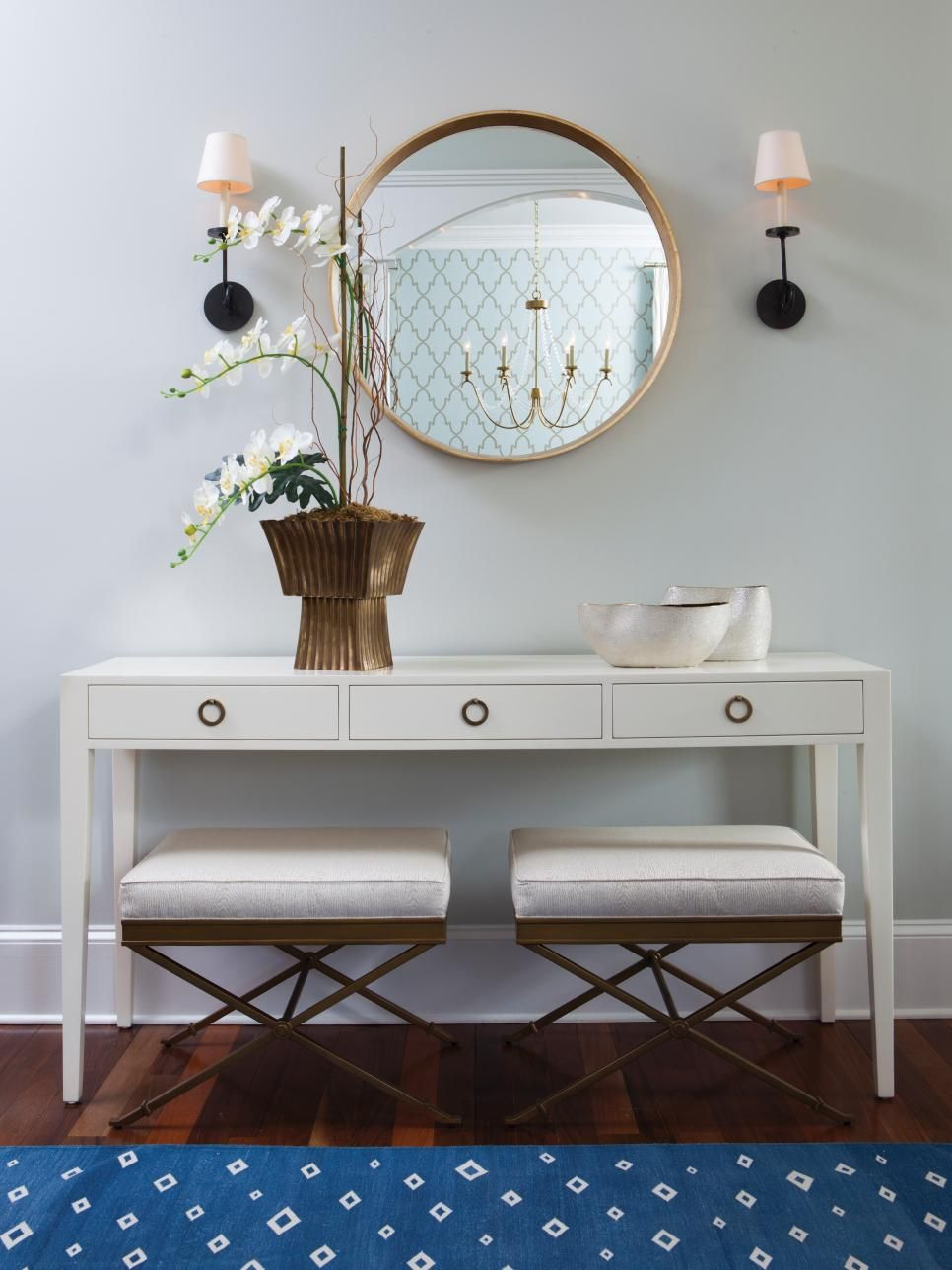 A White Console Table Is Paired With A Round Gold Mirror And Benches In  This Eclectic