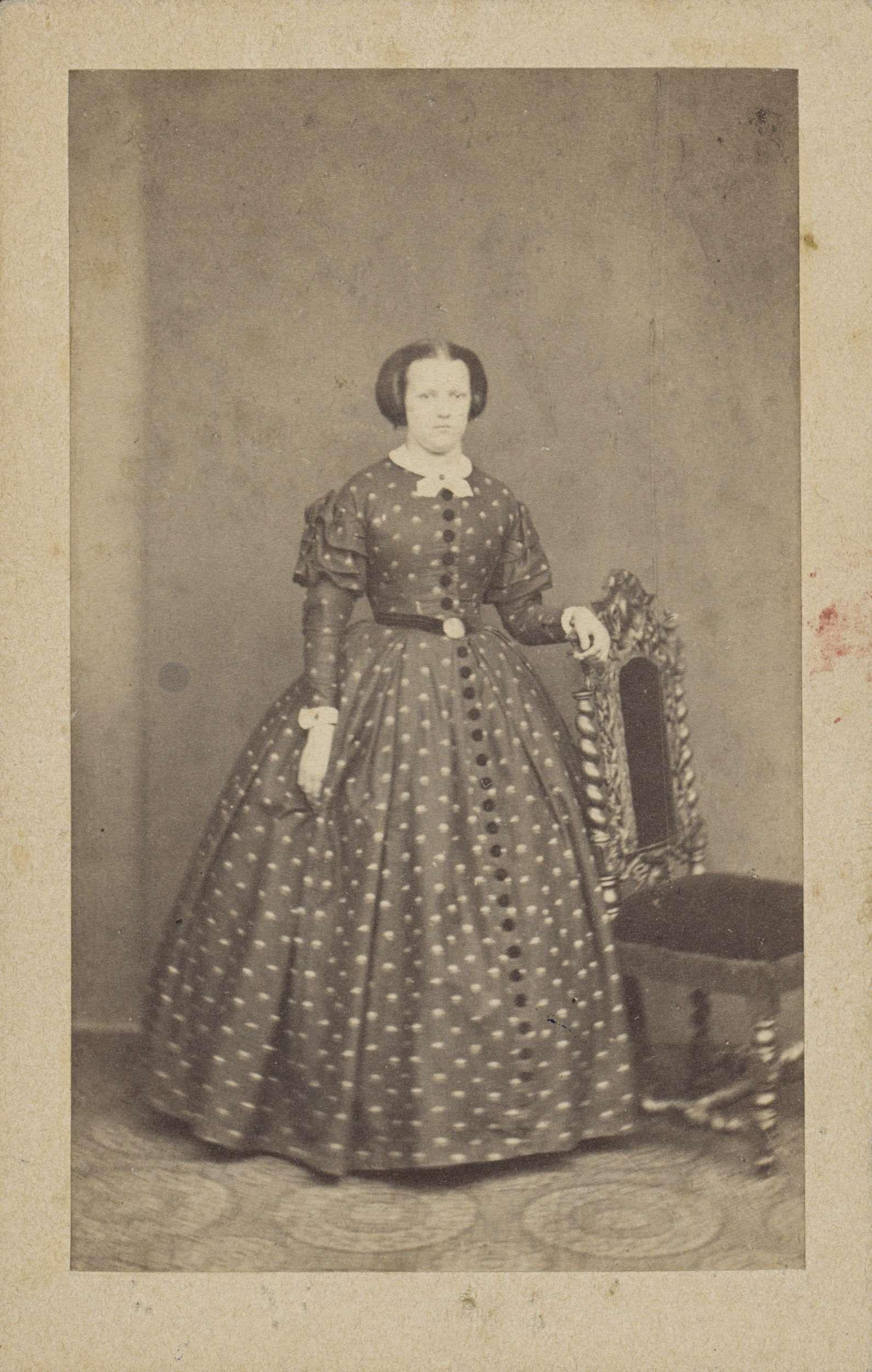 4324c33d0d2ec4 Portret van een vrouw in een lange jurk met stippen en ceintuur ...