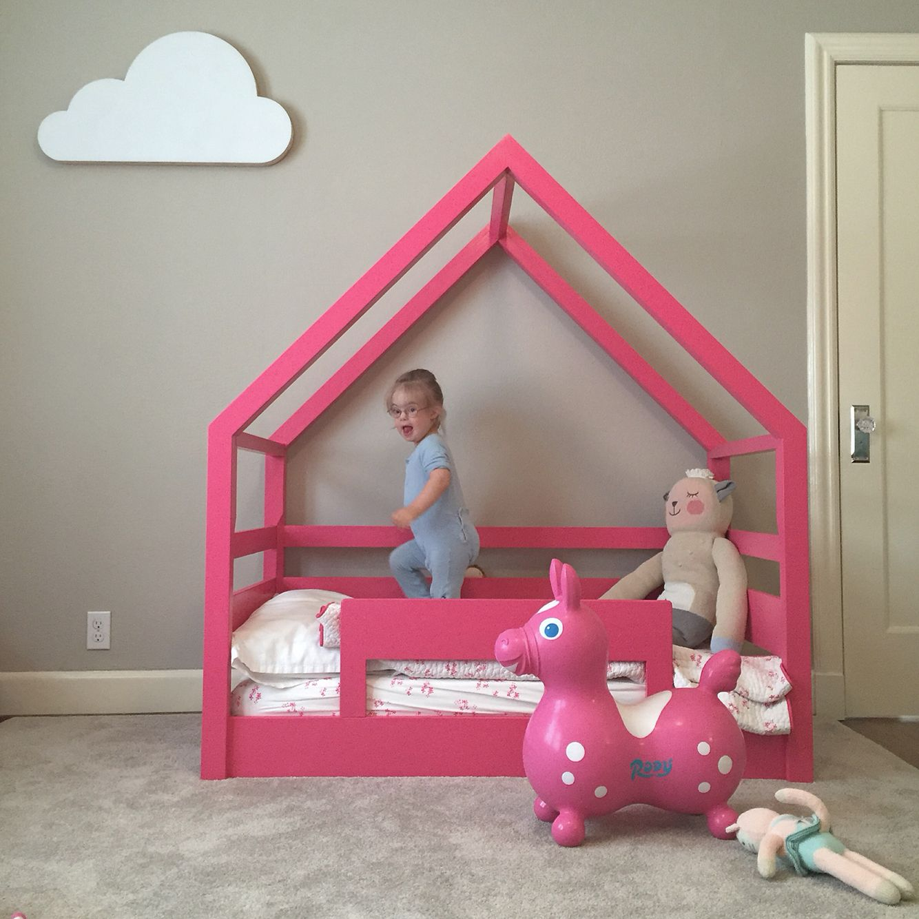 Pink house frame bed and white cloud. Kids bed with rails. Kids house bed. Pink bed. White cloud wall art. By Scott Taylor