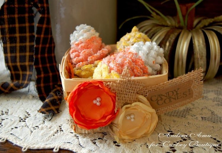 DIY painted and glittered pine cones made to look like candy corn!  Project created by Curtsey Boutique Designer Andrea Amu, featuring wood berry basket, fabric flowers and burlap embellishing.