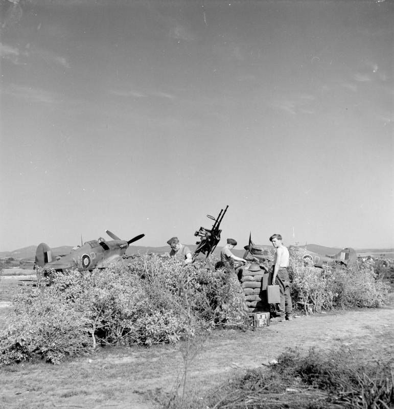Hawker Hurricane Mark IICs of No. 253 Squadron RAF dispersed by a light anti-aircraft gun position, (consisting of twin .303 Browning machine guns), and its crew, at Jemappes, Algeria.