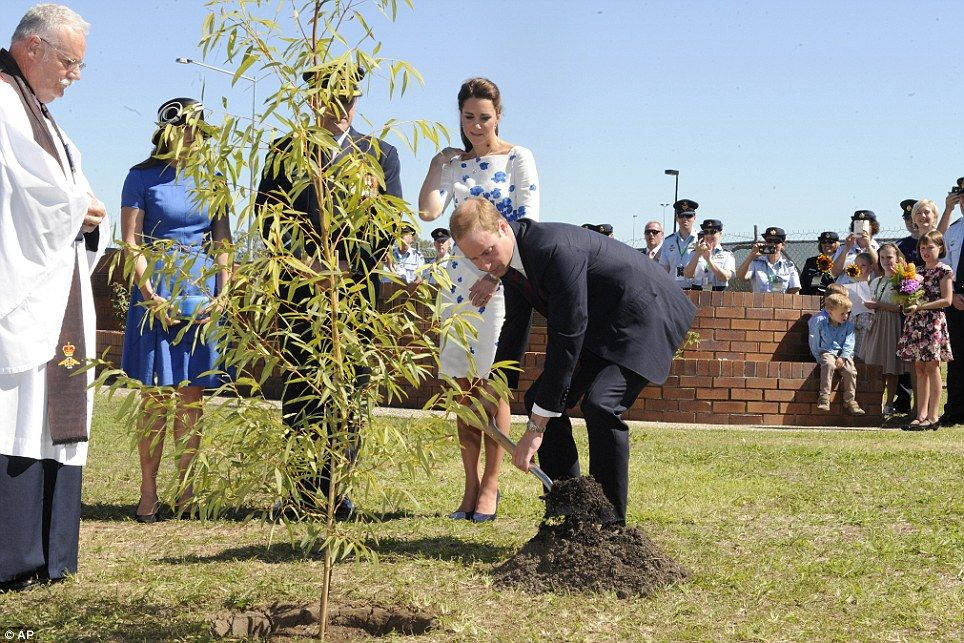 Britain's Prince William plants a Plunkett Mallee tree, watched by his wife Kate, the Duchess of Cambridge, at the Memorial Garden at RAAF B...