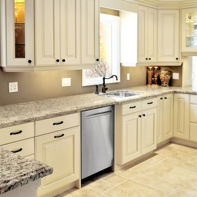 galley kitchen with cream cabinets with brown glaze and tan tile