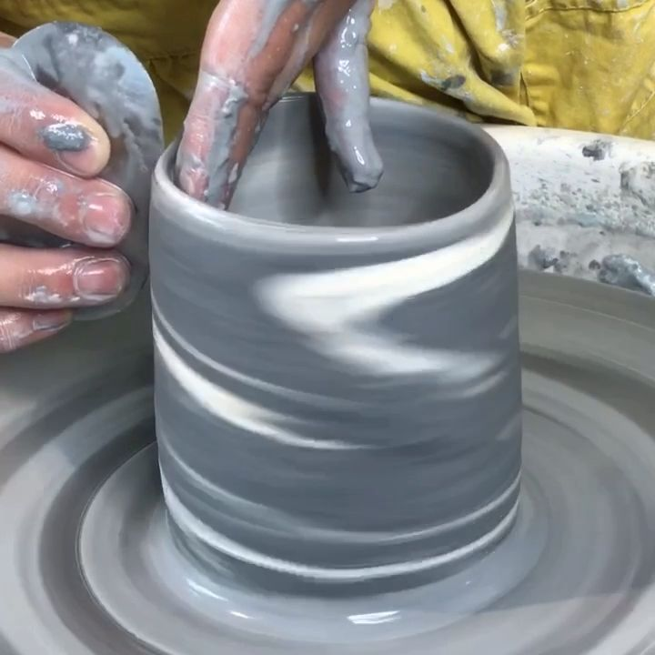 Throwing a marbled porcelain mug on the pottery wheel