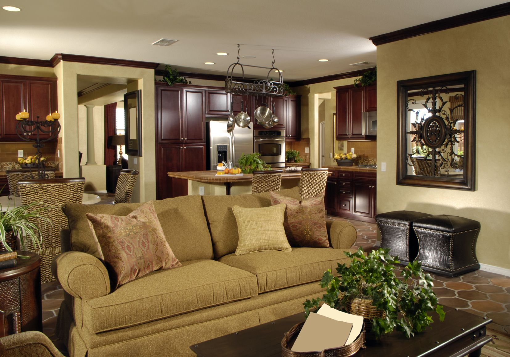 Wood Cabinetry Throughout The Kitchen Area In This Shared Open Space Contrast With Beige Walls And Tile Flooring While Brown Roll Arm Sofa Dark