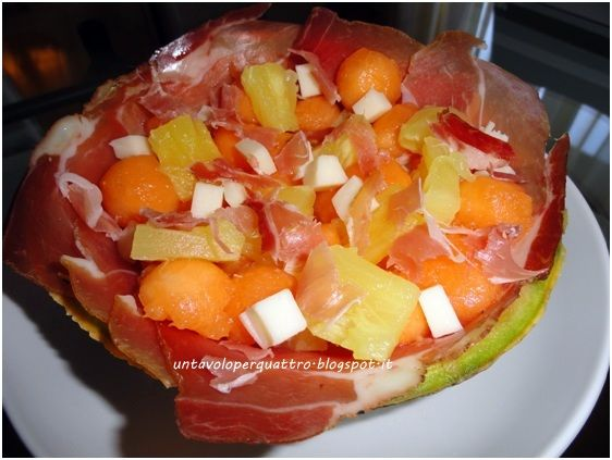 Divide into halves the melon, remove the seeds, dig the pulp and keep it aside. Drain it from the juice and place inside the ham slices, then put provolone