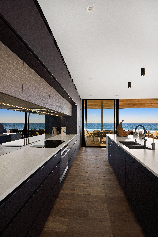 Modern Galley Kitchen With Smokey Mirror Splashback And Black Cabinetry By Woodstock Industries Lu Luxury Kitchen Modern Luxury Kitchens Modern Kitchen Design