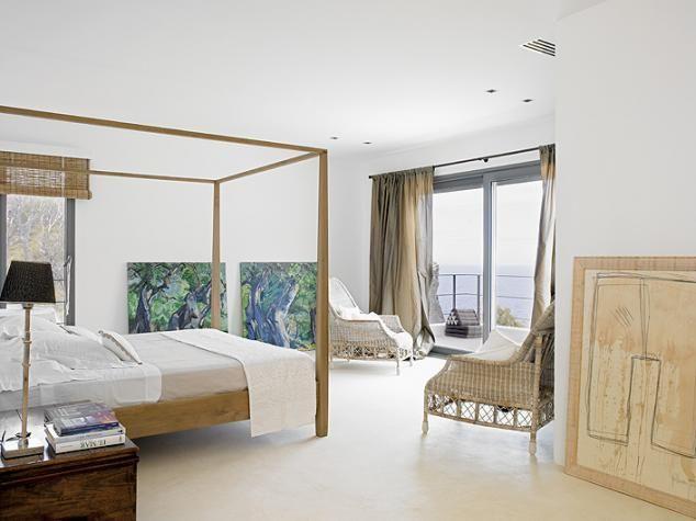 Mniej znaczy więcej. Proste łóżko z baldachimem, wiklinowe fotele i obrazy oparte o ścianę. I tak widoki są tu najważniejsze.