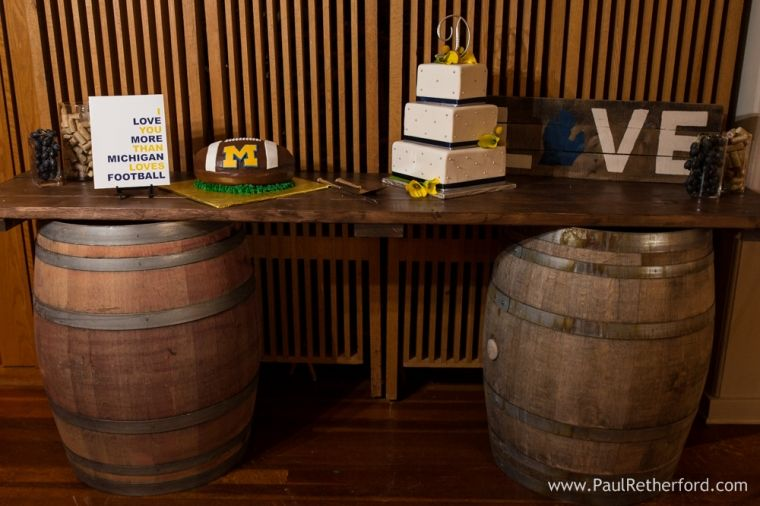 Wedding cake design at Leland Lodge in Northern Michigan with maize and blue theme wine wedding and University of Michigan football groom's cake photo by paul retherford wedding photography #maizeandblue #uofm #puremichigan #lelandwedding #nomiweddings #weddingcake #michiganfootball #groomscake #cake #dessert #wineweddingSweet Petites of Grand Traverse