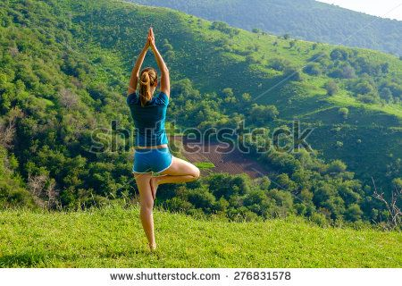 Beautiful young woman practicing yoga at mountains - stock photo