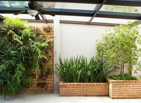 Neste amplo quintal, a parede próxima à churrasqueira recebeu jardim suspenso com peperômias e samambaias. Ao lado, jardineiras com falso-íris, jabuticabeira e grama-amendoim. Foto Edu Castello/Editora Globo