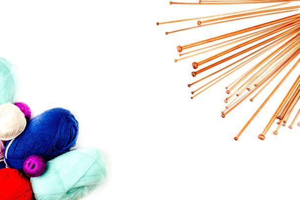 knitting background frame knitting needles and colorful yarn on white