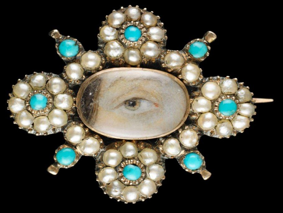 Yellow-gold brooch with border of 32 natural oriental half-pearls in a floral motif with eight small turquoise stones; brown right eye. Oval locket back with woven brown hair under glass. Circa 1820.