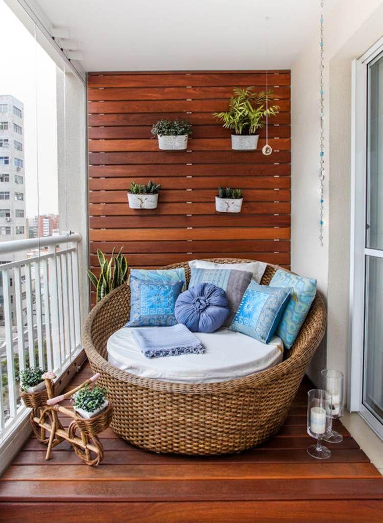 petit jardin à la verticale au petit balcon aménagé avec un grand fauteuil en rotin