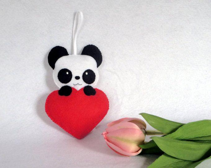 Ce petit panda se cache dans un cœur rouge, avec ses grands yeux ...