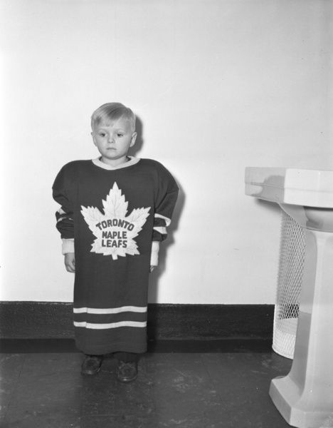 """Walter """"Skippy"""" Peter Stanowski tries on a Maple Leafs sweater at the Stanowski family home in Toronto Jan. 10, 1947. (HHOF/Images on ice)"""