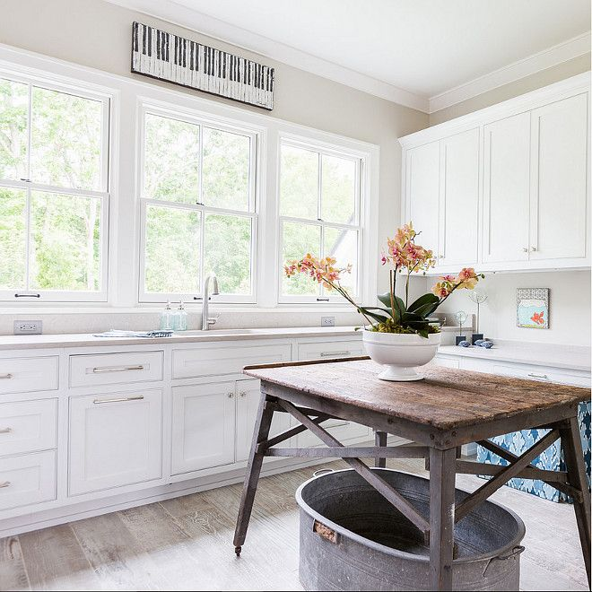 beautiful laundry room with white cabinets stainless steel hardware reclaimed wooden table for folding