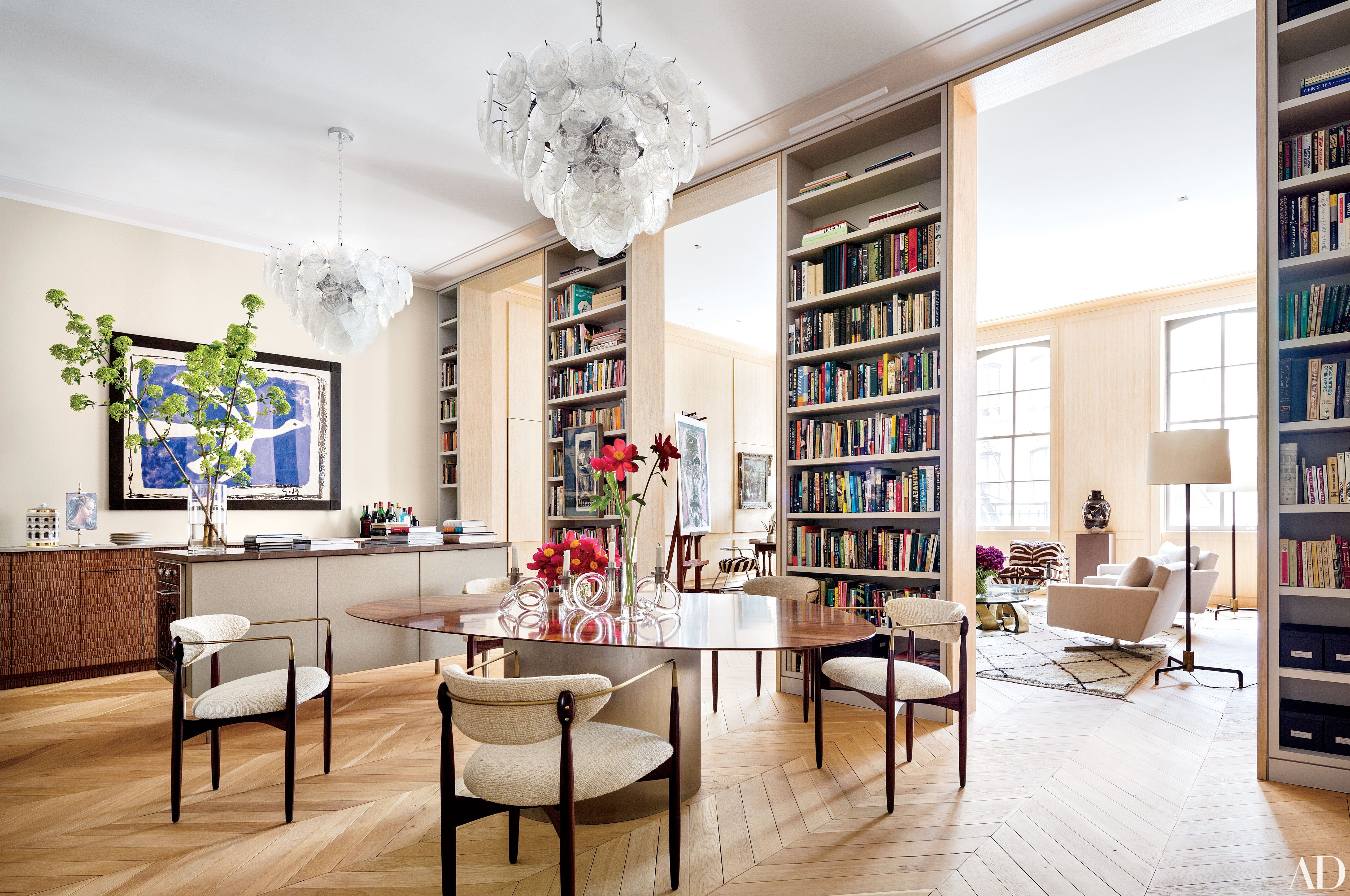In the New York City loft of architect Steven Harris and interior designer Lucien Rees Roberts, monumental bookshelves delineate the living and dining areas, which feature a 1960 Georges Braque print (at left) and Ib Kofod-Larsen chairs at the Rees Roberts + Partners dining table.