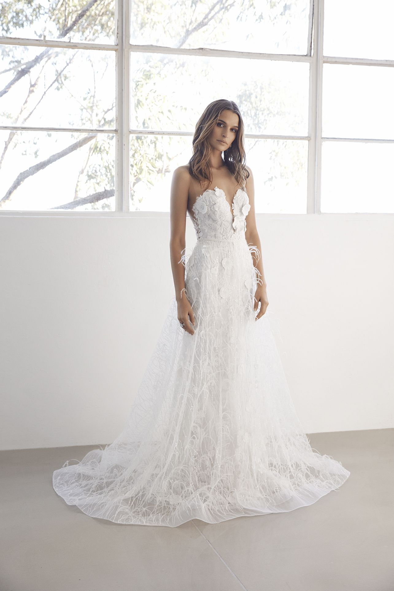 124fb02c340 3D appliqué tulle lace gown with a fit and flare silhouette and illusion  strapless sweetheart neckline. Optional feathered overskirt.