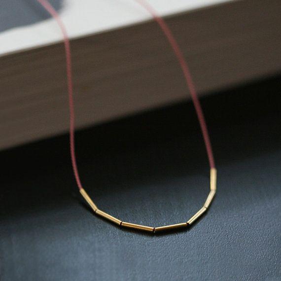 Tällaisen siron kaulakorun voisi varmaan tehdä itsekin silkkinauhasta ja putkimaisista helmistä. Minimalist silk and gold necklace by by elephantine on Etsy, $28.00