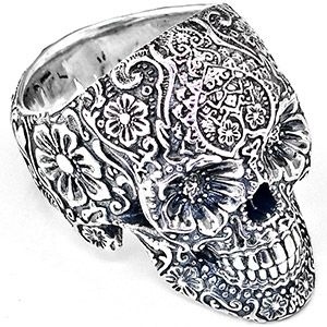 www.inkmetal.com - T.S. Wittelsbach's ornately sculpted sugar skull ring boasts unmatched detail and a motif that blends traditional elements - such as marigolds - with unexpected additions, like the tantric lotus worked into the forehead. A gift to the living, this folkloric calvera is cast in sterling silver – birthstones can also be set into the eyes in commemoration of the dead.