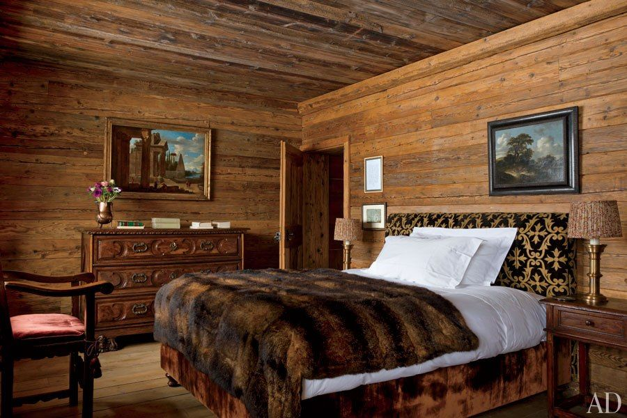 A Rustic Swiss Alpine Hideaway : A master bedroom, lined with pine, features lamps by Studio Peregalli and a 17th-century Italian commode surmounted by an 18th-century capriccio l  Architectural Digest
