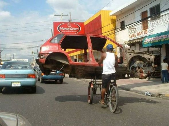 Hombre cono bicicleta transportando un coche