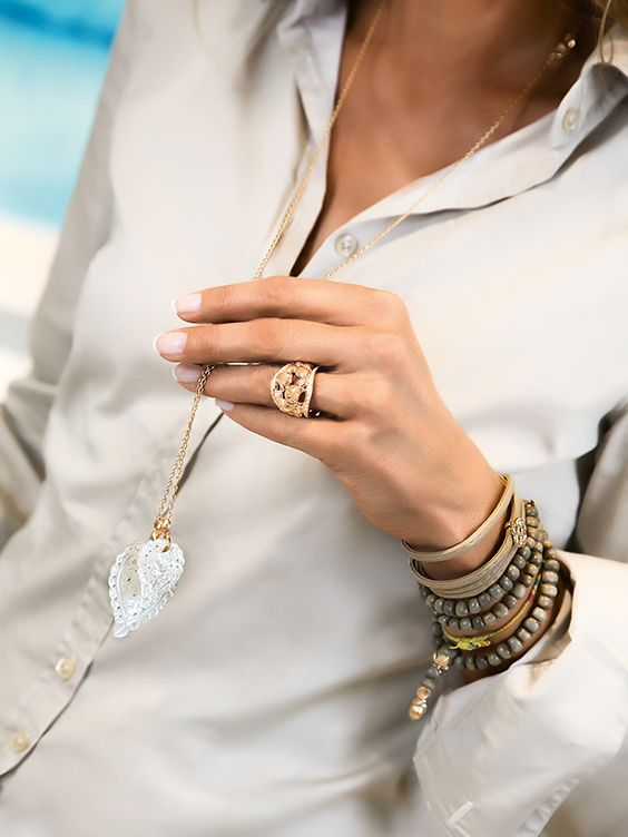 A plain white blouse enhanced by fine jewelry India Leaf pendants