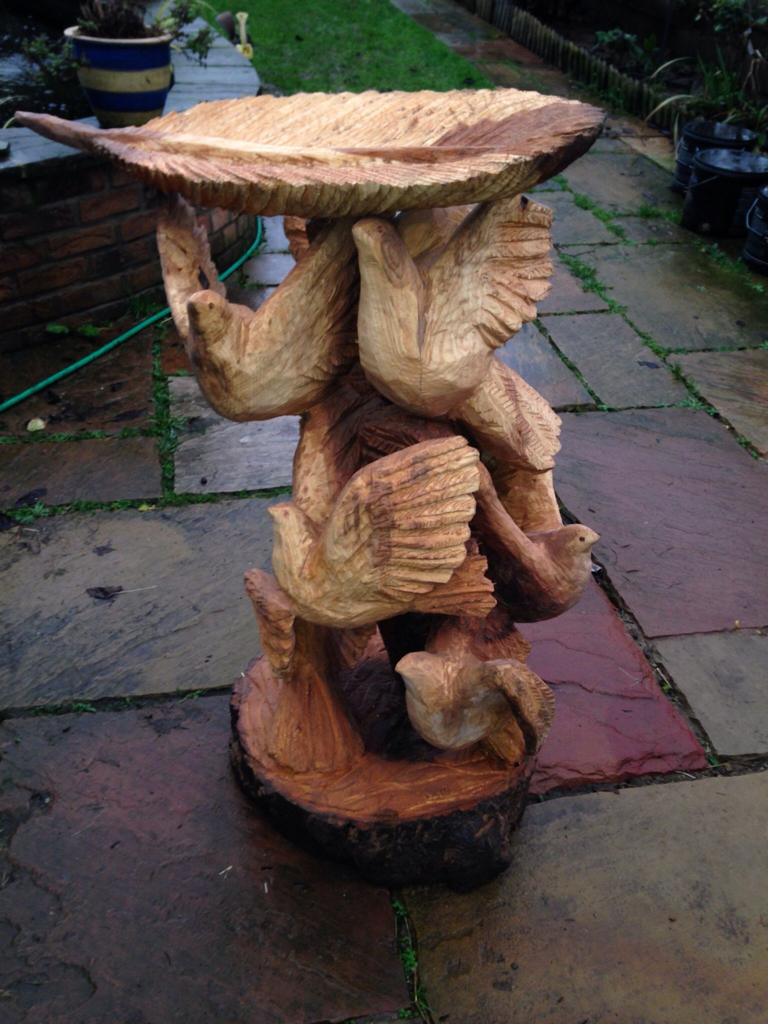 A mumuration bird table carved with chainsaws from piece