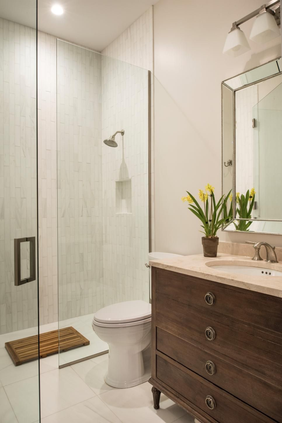 This single vanity neutral bathroom features a glass enclosed shower ...