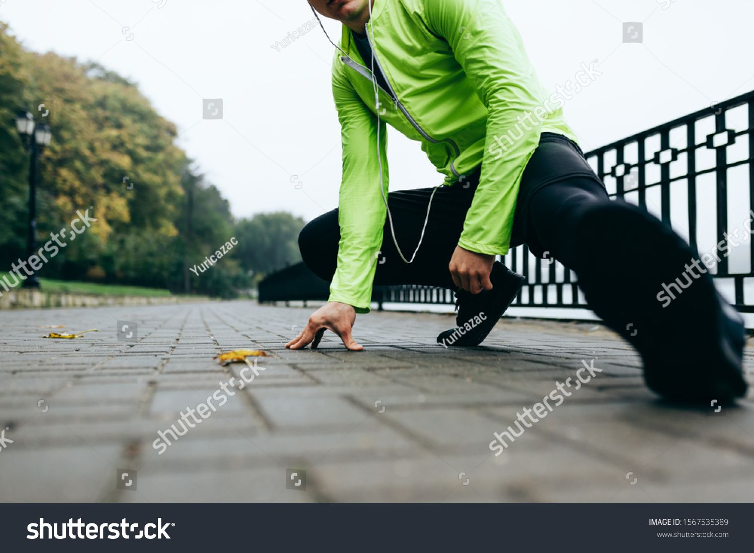Cropped head image of sportsman stretching outdoor in the city lake background. Fitness male exercis...