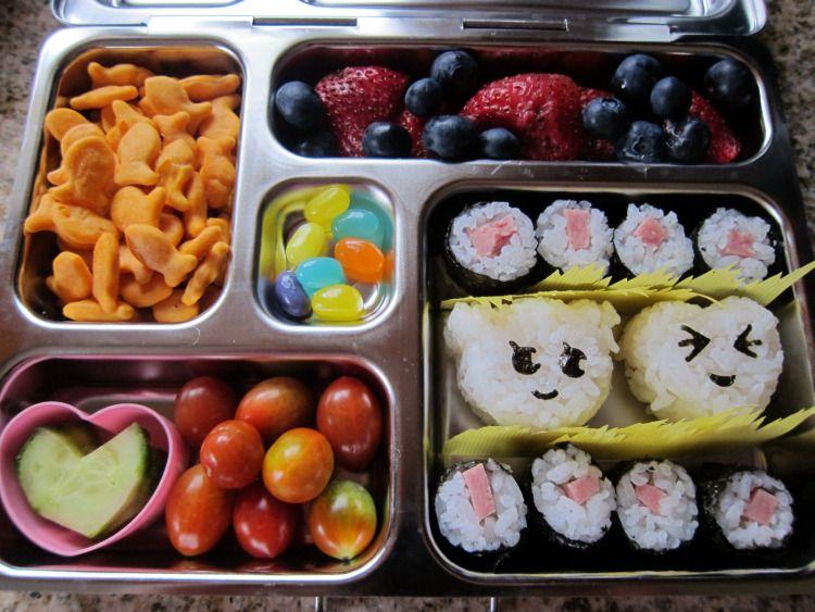 Spam sushi rolls, heart- and bear-shaped rice balls with nori punch expressions, heart-shaped cucumbers, tomatoes, Goldfish, fruit, jellybeans in a #planetbox #bento