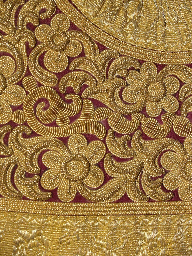 Detail of gold embroidery on red velvet ground on a vest pirpiri