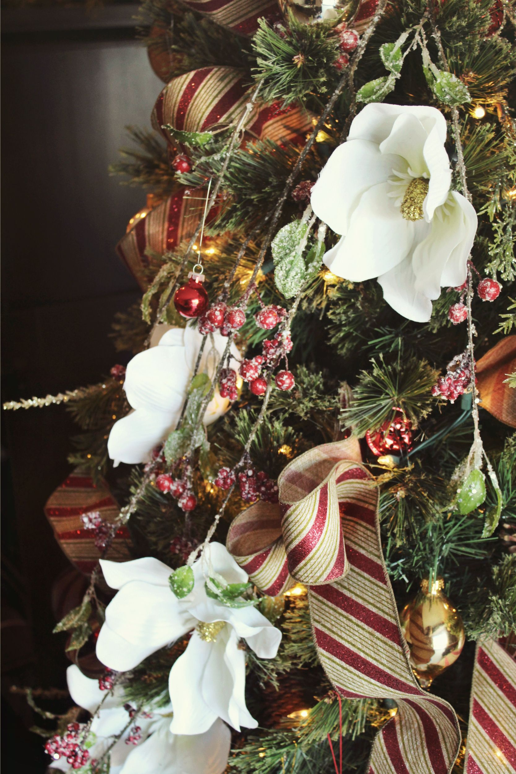 White Magnolia Flowers And Frosted Berry Branches Cascade Down This Christmas Tree Christm Christmas Tree Flowers Christmas Tree Decorations Tree Decorations