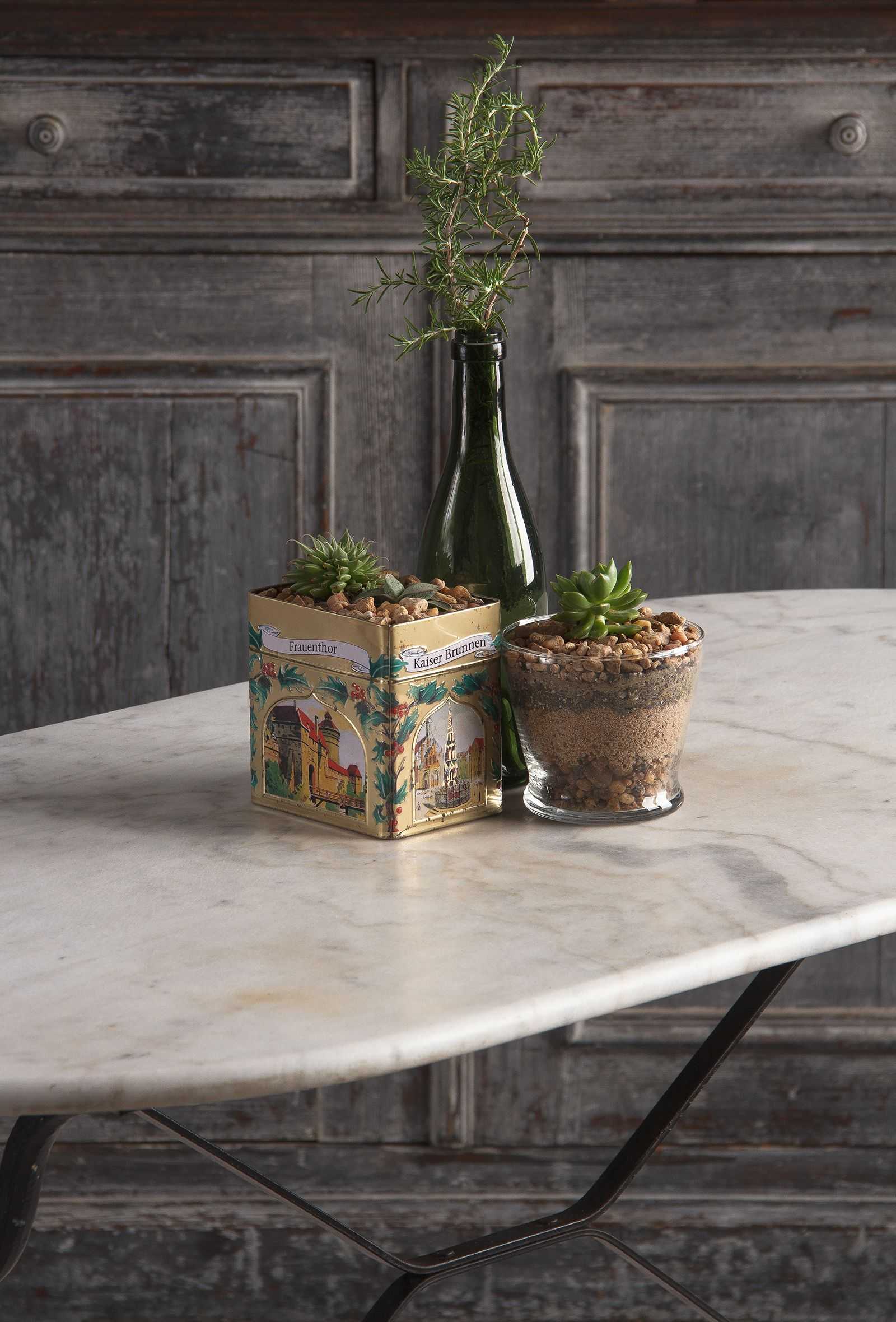 Beautiful table centerpiece for the home. Using vintage pieces as unique planters and vases showcases personal style and brings history into a new home!   French Bistro Table with Iron Base and Oval Marble Top, 1940s Vintage Vinegar Bottle #vignettestyling #interiordesignideas #antiquedecor #tabledesign #indoorplants #centerpiecesforparty #vintagevinegarbottle