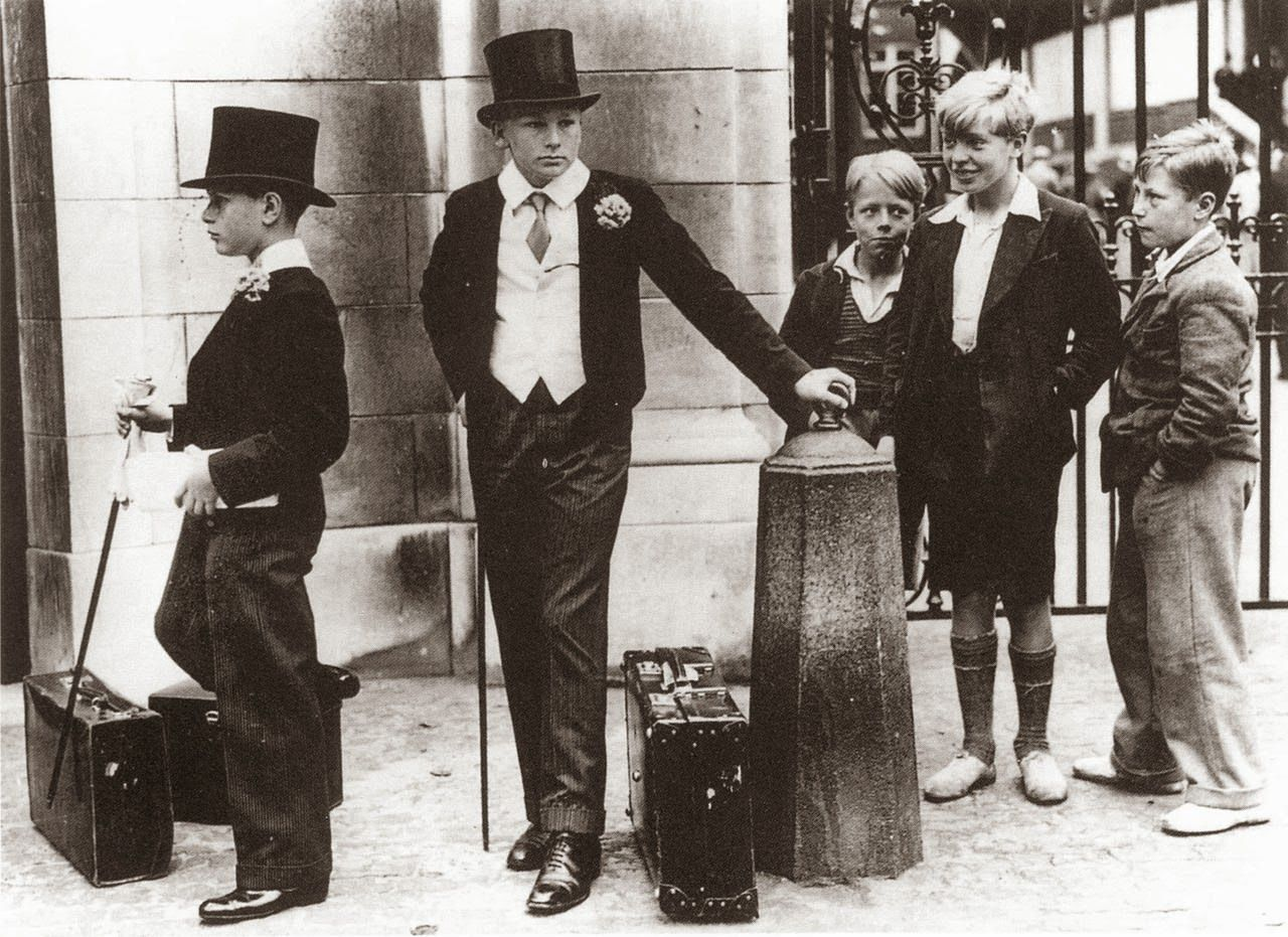 """Toffs and Toughs"" is a 1937 photograph of five boys: two dressed in the Harrow School uniform including waistcoat, top hat, boutonnière, and cane; and three nearby wearing the plain clothes of pre-war working class youths. The picture was taken by Jimmy Sime on 9 July 1937 outside the Grace Gates at Lord's Cricket Ground during the Eton v Harrow cricket match. It has been reproduced frequently as an illustration of the British class system."