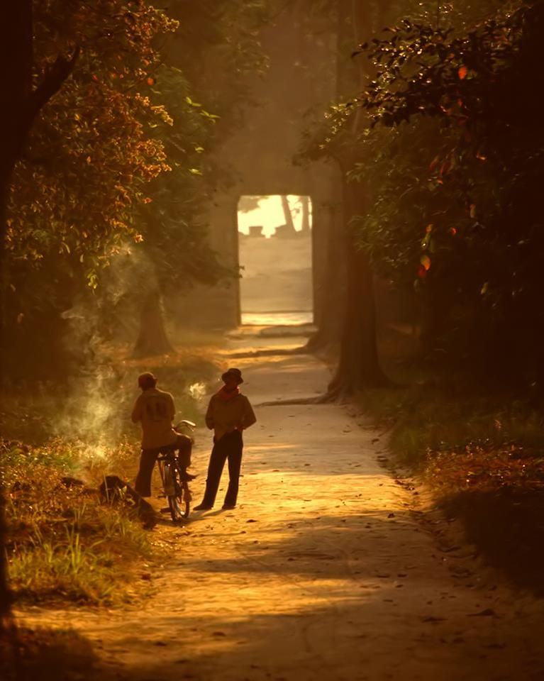 Two men take a smoke break as the sun spreads it's golden warmth over the Temples of Angkor, Cambodia