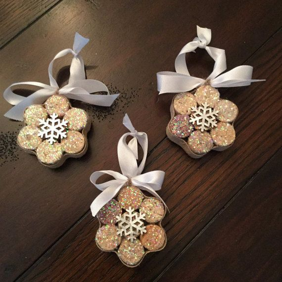 These snowflake ornaments are made from upcycled wine corks. They come in sets of 3, and all 3 will look like the one pictured. These are sturdy and held together with glue and surrounded by glued-on ribbon. These ornaments look beautiful on the tree as the iridescent glitter catches the light, creating a lovely sparkle and shine.