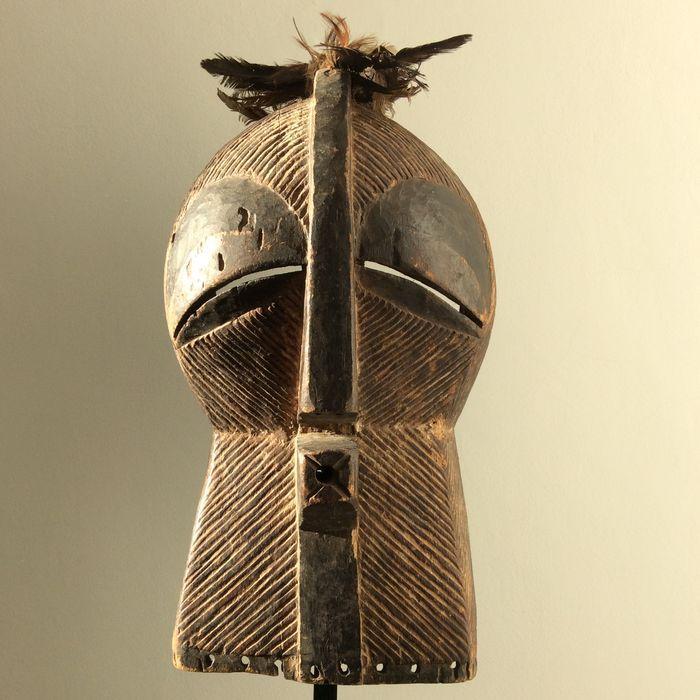 De LUBA hebben een matrilineaire afstammingscultuur . Bij hun maskers ligt dan ook het accent op de ronde , vrouwelijke vormen. Onze variant behoudt in het bovenste gedeelte nog steeds deze ronde basisvorm aan. Het onderste deel van het masker verraadt echter de SONGYE-invloed  Typisch LUBA is dan weer dat er bovenaan het kammetje een inkeping werd gemaakt met twee gaatjes , om met een touwtje  een bundeltje pluimen aan te brengen. De verdiepte maskerrand werd van aanhechtingsgaten voorzien…