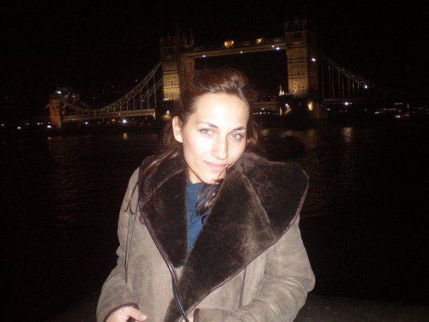 grey shearling coat with leather details by the Thames river, London