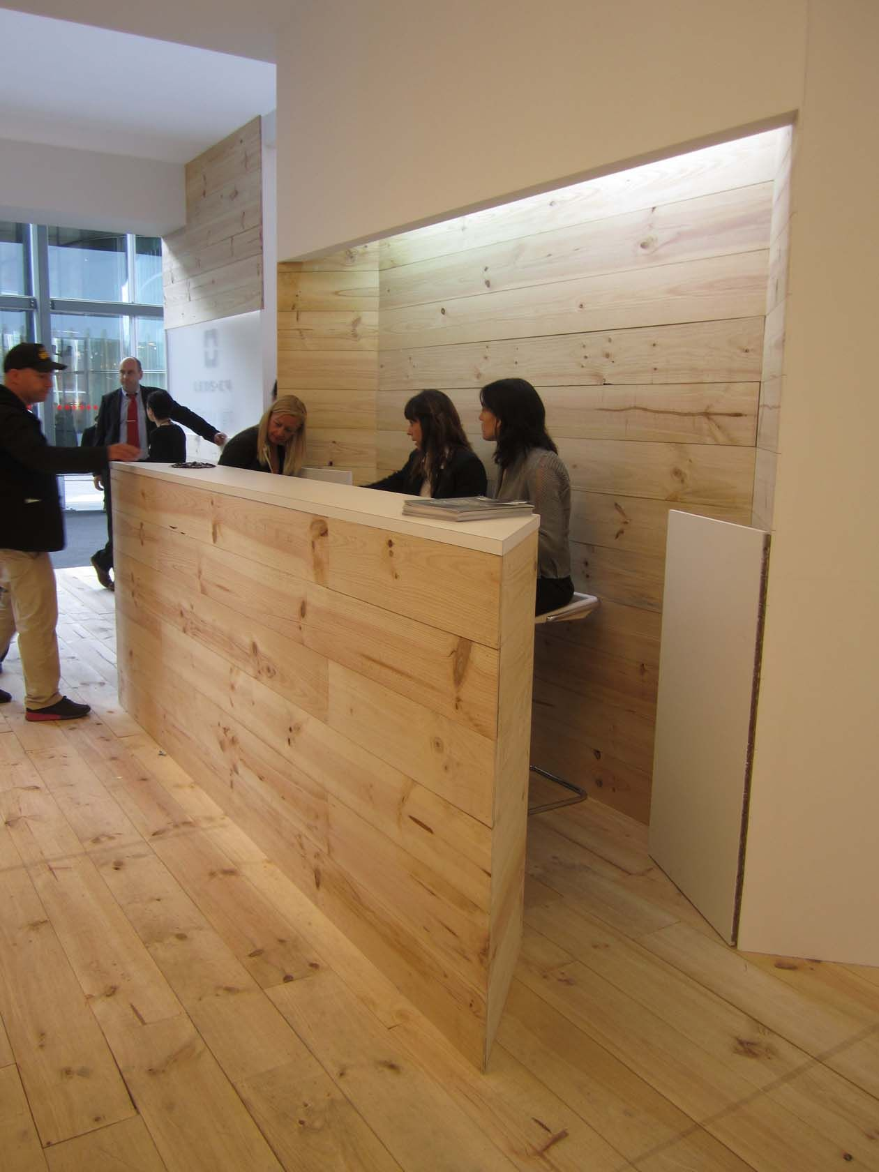 stand up reception, yin yang space carved behind desk to capture  receptionists