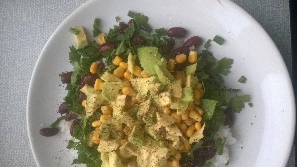 sałatka z ryżu, fasoli, kukurydzy  i awokado, podana ze świeżymi ziołami (pietruszka, zielona cebulka), skropiona cytryną, z solą i pieprzem