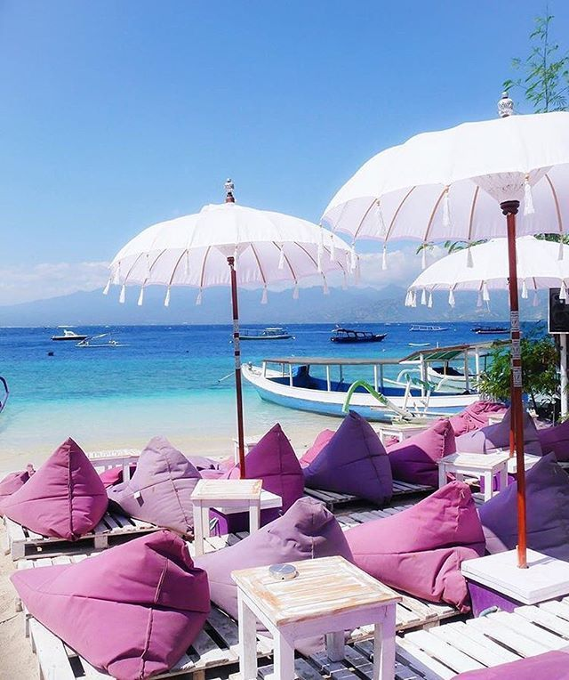 Pink and white umbrellas on the beach of Gili Islands in Indonesia